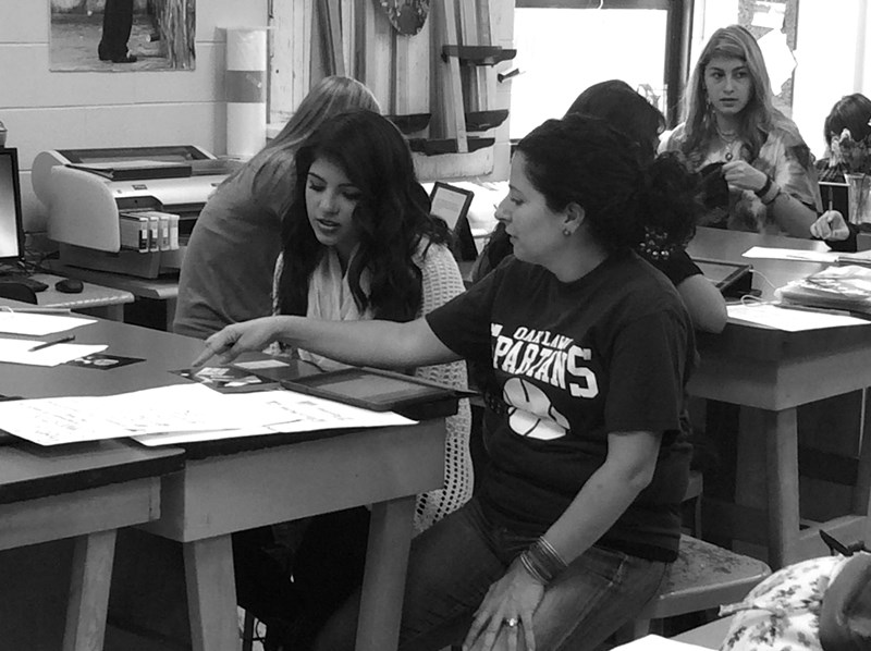 Mrs. Wargin works with a student in her Photography I class